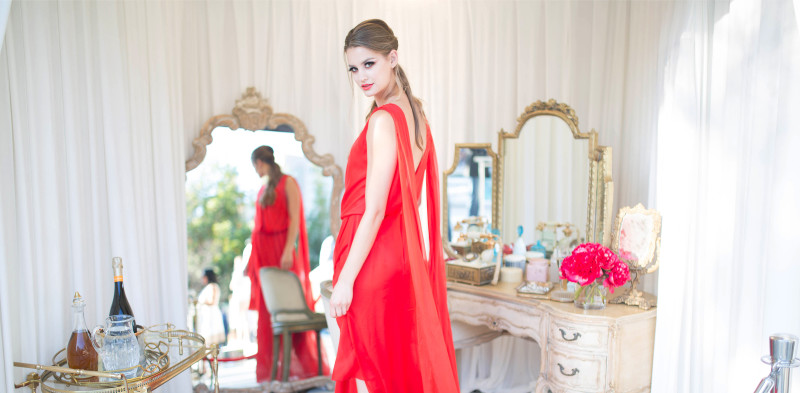 Model in red flowing dress and mirror
